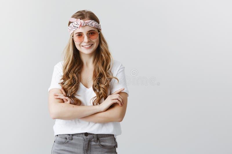 A menina na moda gosta expresso ela mesma com roupa Mulher satisfeito feliz na faixa na moda e nos óculos de sol que guardam cruz fotografia de stock