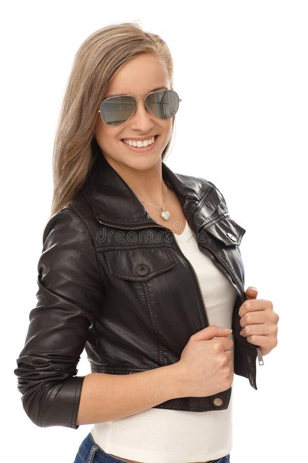 Menina na moda no revestimento de couro e nos óculos de sol fotos de stock