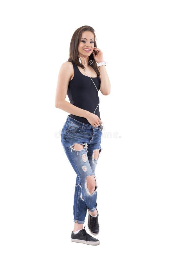 Menina na moda relaxado em calças de brim rasgadas que fala no telefone usando fones de ouvido fotografia de stock