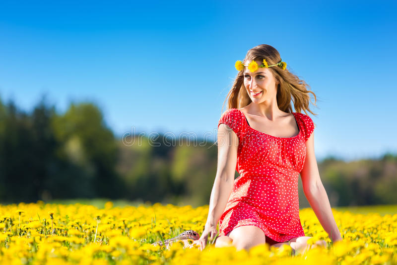Menina na mola em um prado da flor com dente-de-leão imagem de stock