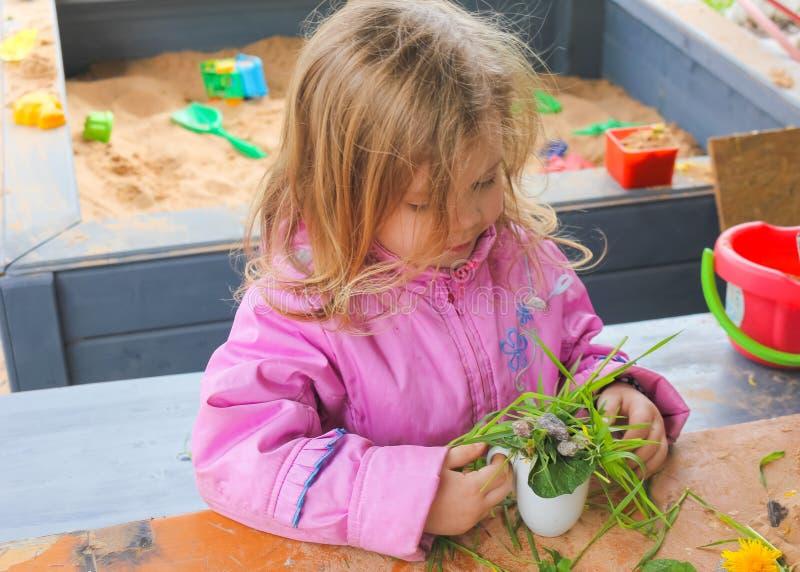 A menina na natureza na tabela, jogando com areia, planta a imagem de stock