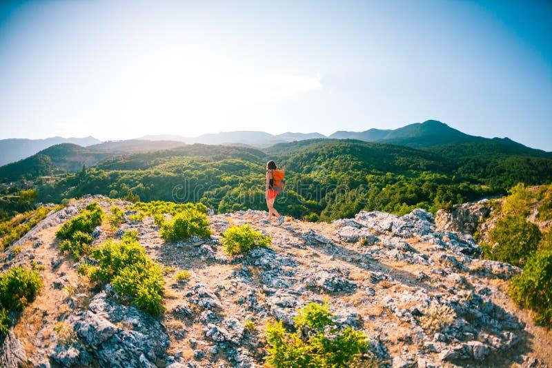 Menina na parte superior da montanha Uma mulher com uma trouxa está estando em uma rocha Escalada à parte superior Curso aos luga fotografia de stock