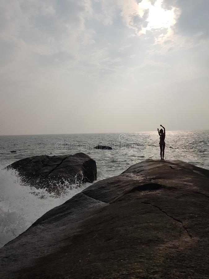 A menina na pedra e na onda foto de stock royalty free