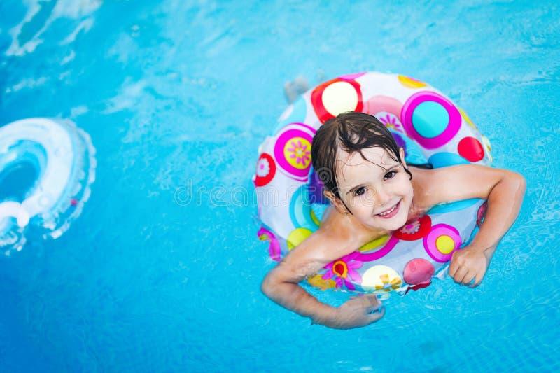 Menina na piscina com anel do flutuador fotografia de stock