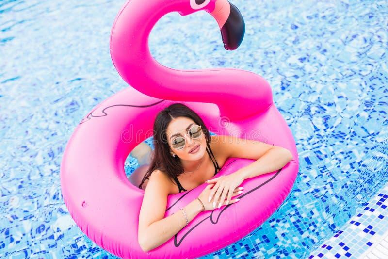 Menina na piscina no flamingo inflável Menino e meninas que sentam-se na mesa surfando e no olhar no mar azul fotos de stock royalty free