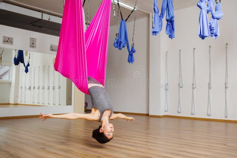 Menina na pose de cabeça para baixo na rede com olhos fechados imagens de stock royalty free