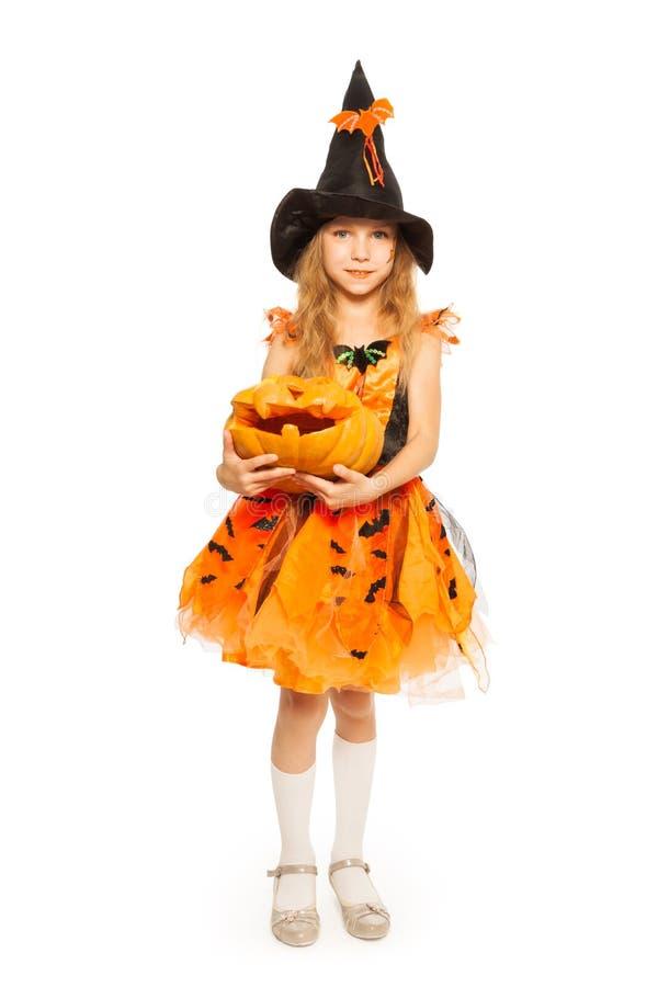 A menina na posse do vestido da bruxa cinzelou a abóbora de Dia das Bruxas imagens de stock