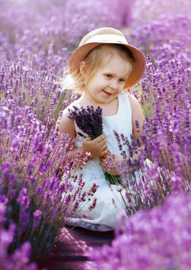 A menina na posse vestindo do chapéu do campo da alfazema floresce fotos de stock royalty free
