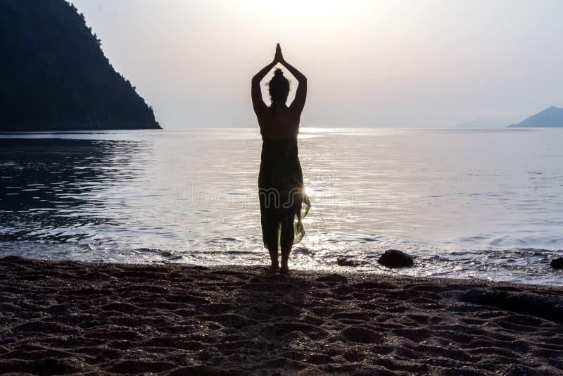 A menina na praia é contratada na ioga, silhueta foto de stock royalty free