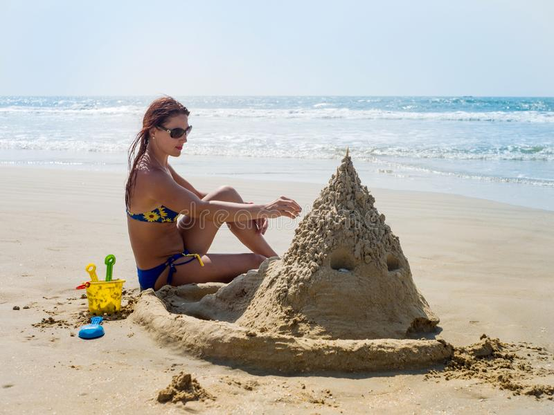 A menina na praia constr?i um castelo da areia foto de stock