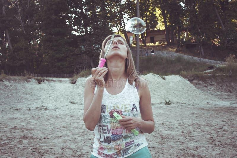 A menina na praia deixou bolhas de ar render foto de stock