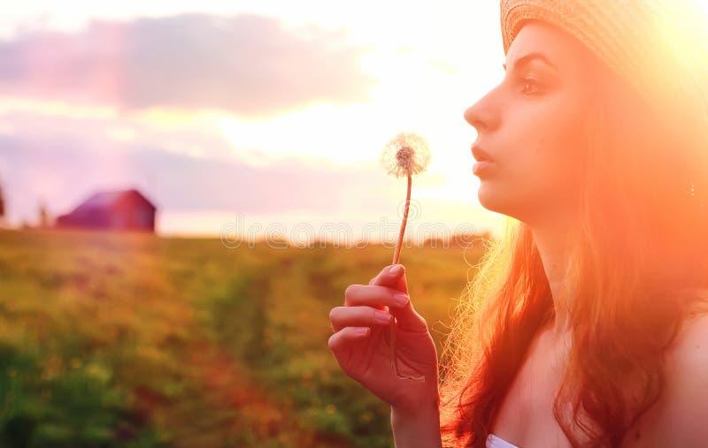 Menina na primavera no campo Uma menina com uma mala de viagem anda th foto de stock