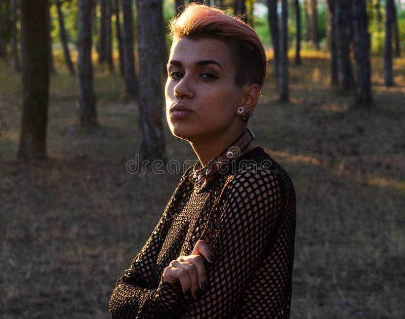 Menina na rede preta no corpo despido Menina punk bonita nova no colar e no pano preto com cabelo cor-de-rosa na floresta do pinh imagem de stock