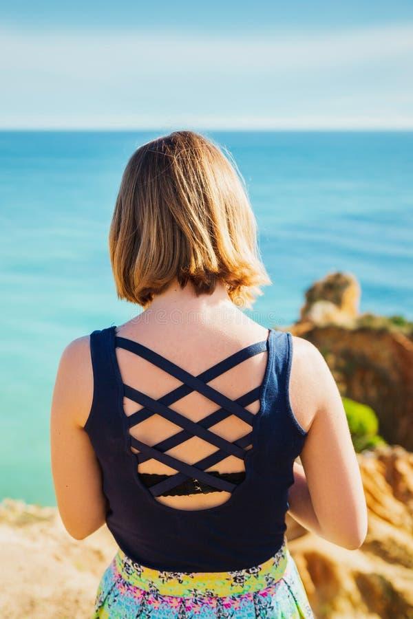 Menina na rocha que olha o mar foto de stock