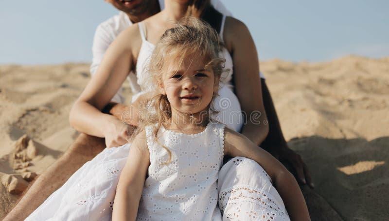 A menina na roupa branca está sentando-se junto com a mãe e o pai na duna de areia do deserto fotografia de stock