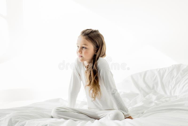 Menina na roupa de noite branca que senta-se na cama em casa imagens de stock