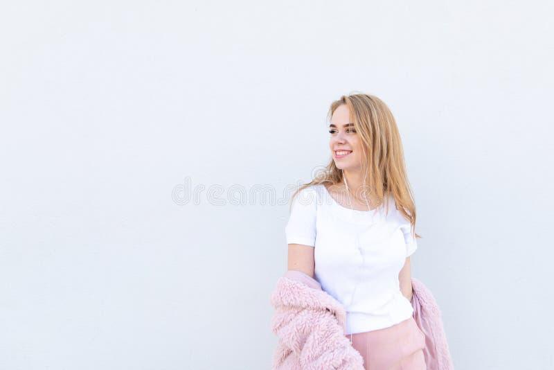 A menina na roupa e em fones de ouvido leves à moda levanta em um fundo branco e olha lateralmente no copyspace imagem de stock royalty free