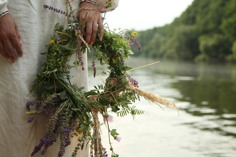 A menina na roupa eslavo com uma grinalda no fundo do rio fotografia de stock royalty free