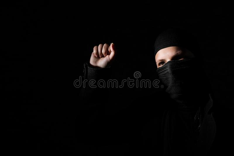 Menina na roupa preta com os protestos escondidos da cara que aumentam o punho no fundo preto com espaço da cópia fotografia de stock royalty free