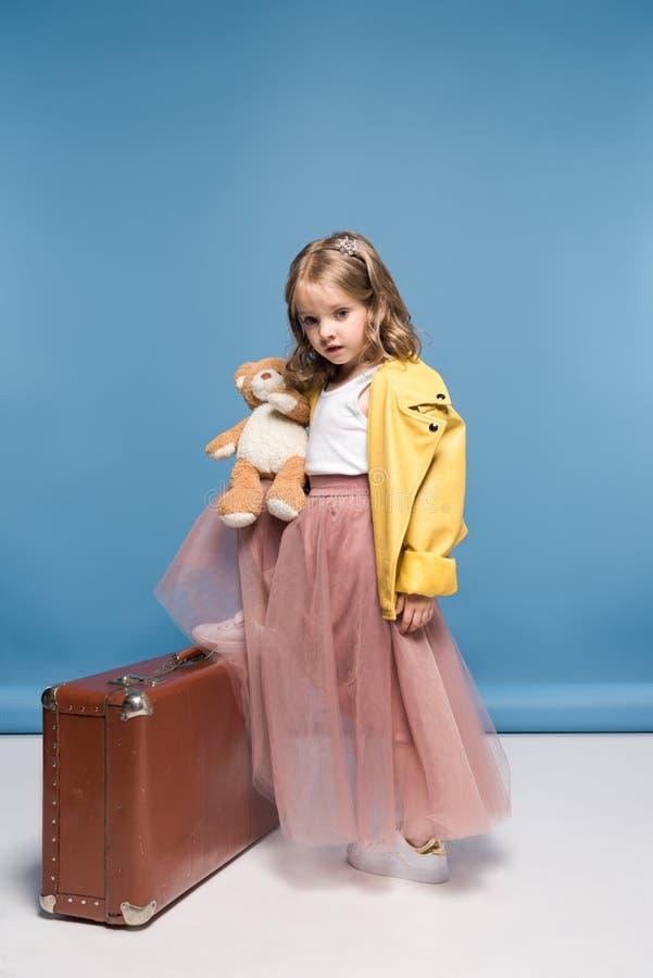 Menina na saia cor-de-rosa que levanta com urso e mala de viagem de peluche fotografia de stock