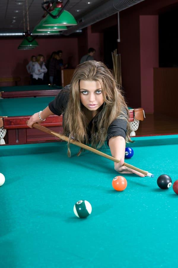 Menina na saia curta que joga o snooker imagem de stock royalty free
