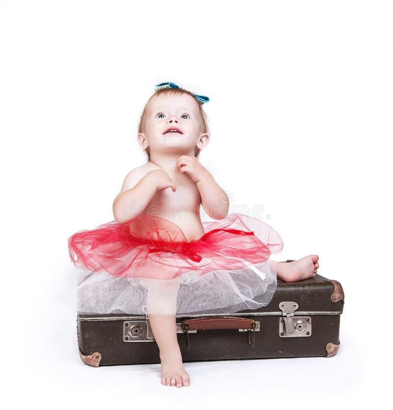 Menina na saia do tutu que senta-se na mala de viagem retro fotos de stock royalty free