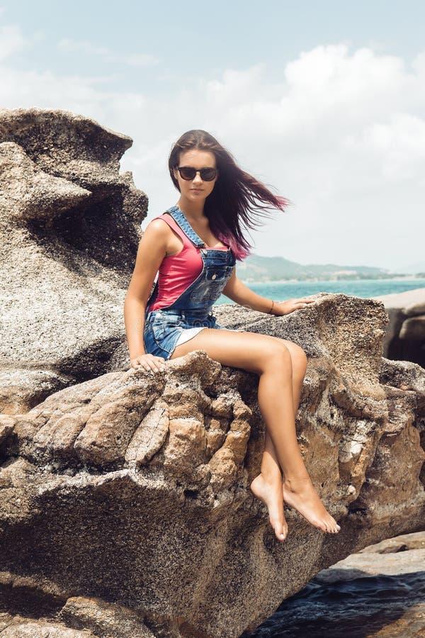 Menina na sarja de Nimes total na praia da rocha fotografia de stock royalty free