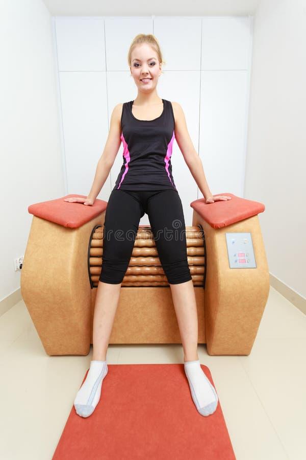 A menina na utilização do sportwear relaxa o salão de beleza saudável dos termas do equipamento da massagem imagem de stock royalty free
