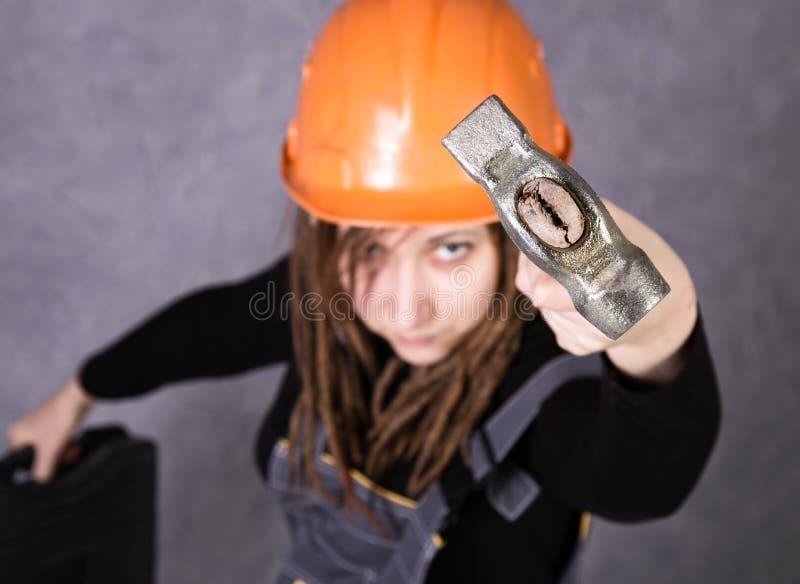 Menina na veste alaranjada do capacete de segurança que guarda a ferramenta do martelo imagem de stock