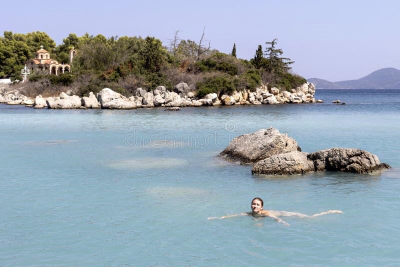 A menina nada no mar foto de stock