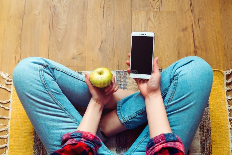 Menina nas calças de brim com o telefone e a maçã verde que sentam-se em um assoalho no tapete lifestyle foto de stock royalty free