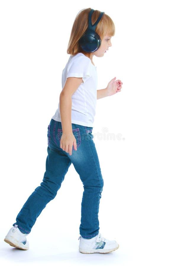 Menina nas calças de brim e em fones de ouvido pretos grandes fotos de stock