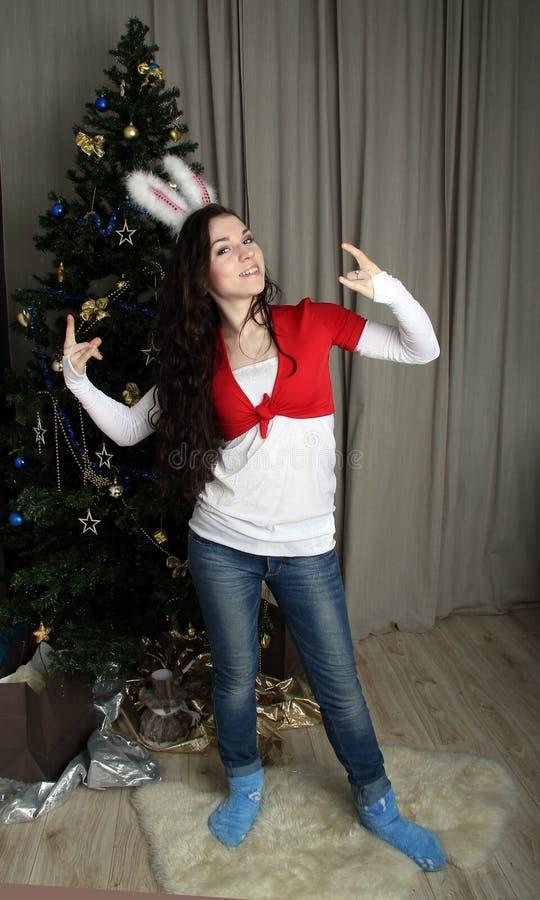 Menina nas calças de brim e nas orelhas de uma lebre fotografia de stock