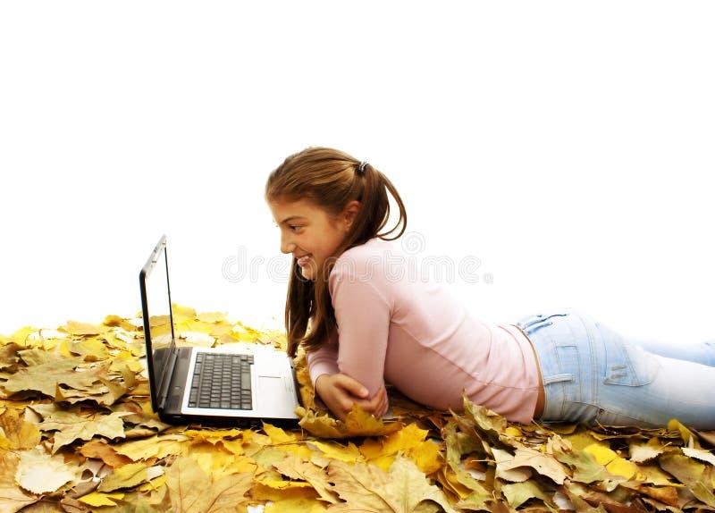 Menina nas folhas de outono com portátil fotos de stock royalty free