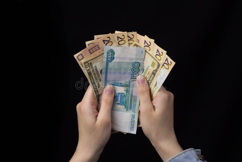 Menina nas mãos que guardam o dinheiro, o euro, os rublos e os dólares, fundo preto, finança do close-up fotografia de stock