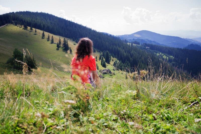 A menina nas montanhas, um viajante fotografou da parte traseira imagens de stock