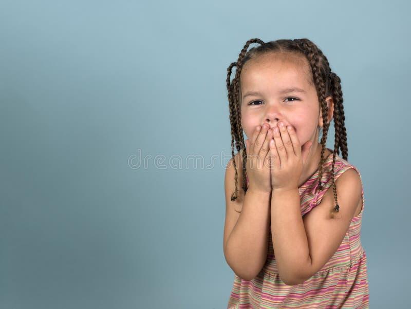 Menina nas tranças que ri atrás de suas mãos fotos de stock