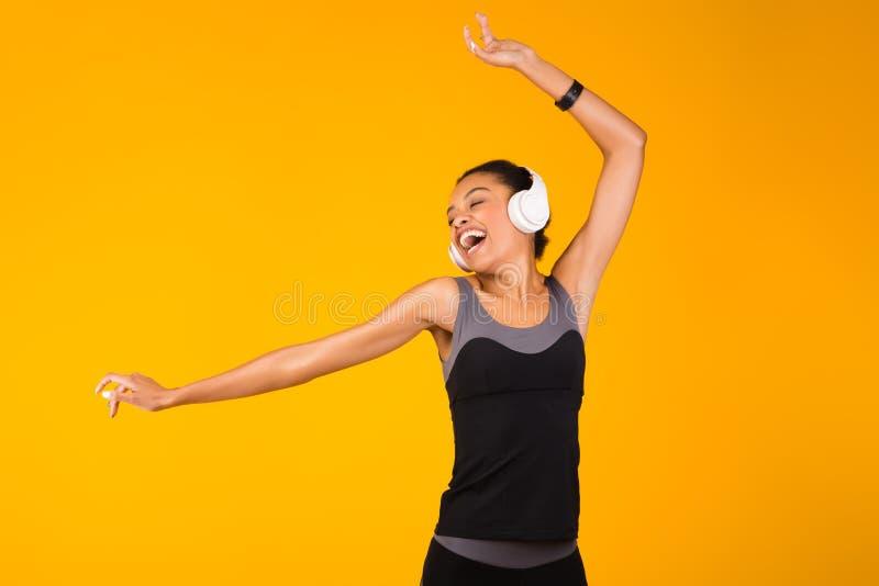 Menina Negra Em Fones Sem Fio Dançando E Cantando, Fundo Amarelo fotografia de stock