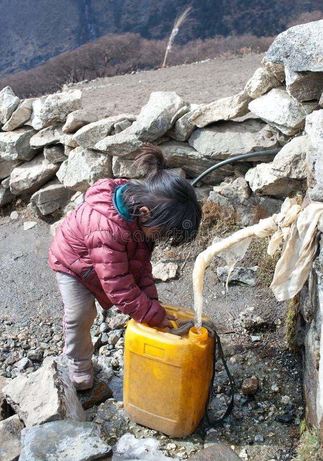 A menina nepalesa pequena derrama a água de uma água-bomba imagens de stock