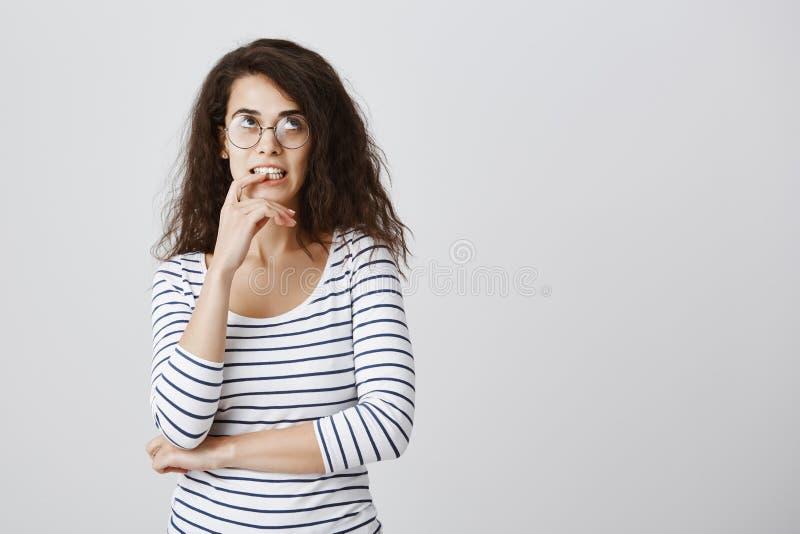 Menina nerdy atrativa que tenta calcular na mente Retrato da fêmea encaracolado-de cabelo bonito mantida distraído focalizada nos foto de stock