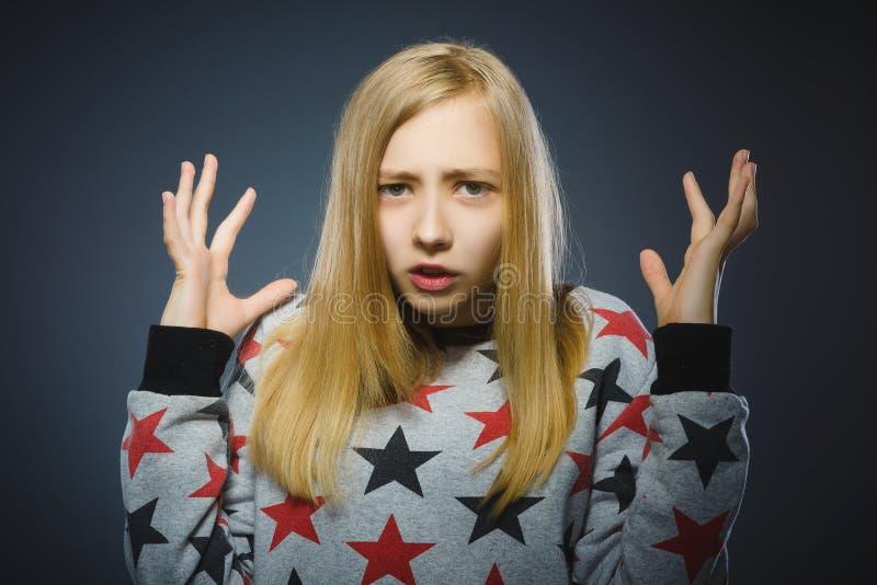 Menina nervosa hesitante incerto nova do retrato do close up no cinza imagem de stock