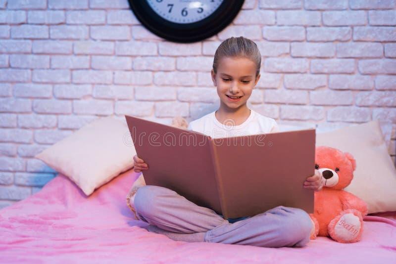 A menina, neta é livro de leitura na noite em casa fotografia de stock