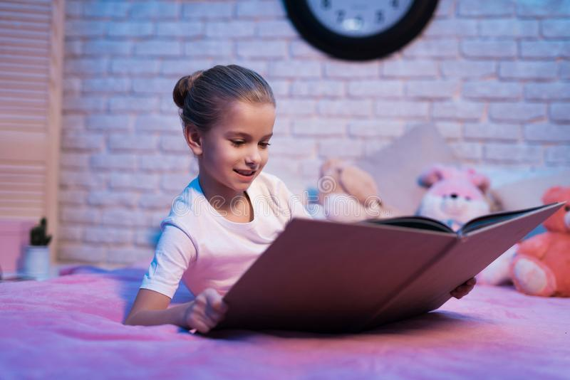 A menina, neta é livro de leitura na noite em casa fotos de stock royalty free