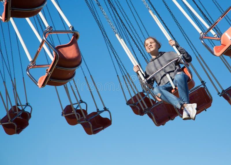 A menina no balanço Atração no parque fotografia de stock royalty free