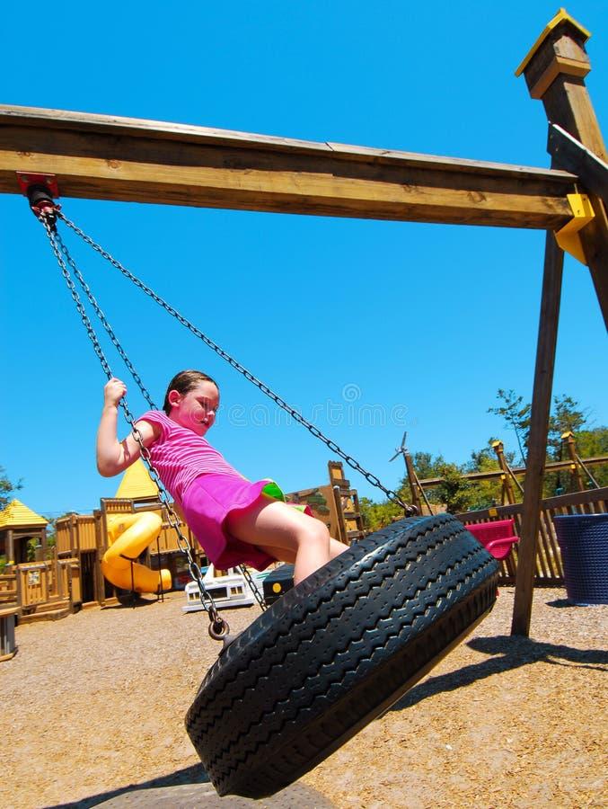 Menina no balanço do pneu do parque fotografia de stock