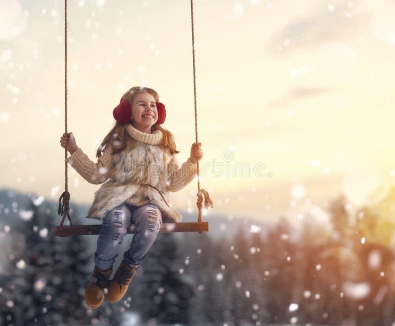 Menina no balanço no inverno do por do sol imagem de stock royalty free