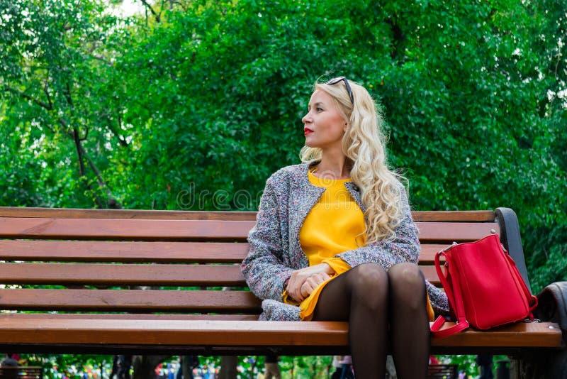 A menina no banco está esperando o indivíduo Uma jovem senhora bonita em um vestido amarelo está descansando no parque foto de stock royalty free