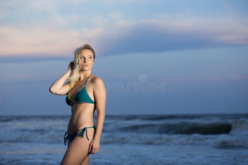 Menina no biquini azul na praia imagens de stock