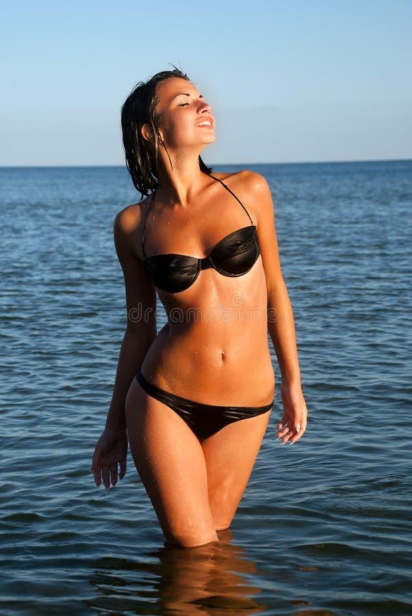 Menina no biquini preto com mar imagem de stock