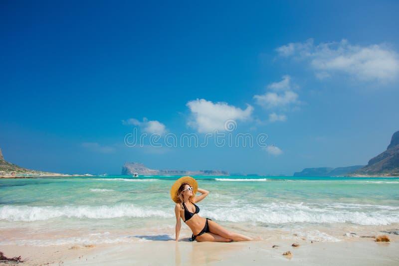 Menina no biquini preto e com o chapéu na praia de Balos foto de stock